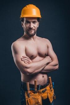 Muskularny pracownik budowlany. młody pewny siebie mężczyzna trzymający skrzyżowane ręce i patrzący w kamerę podczas stania