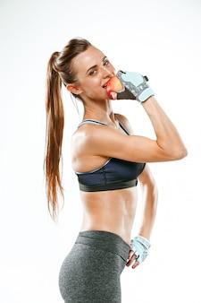 Muskularny sportowiec młoda kobieta na białym tle