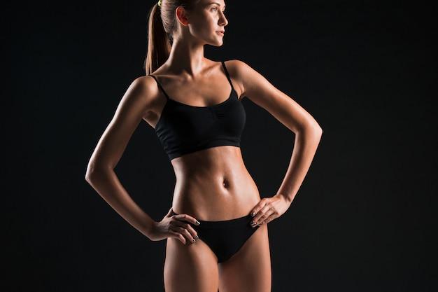 Muskularny sportowiec młoda kobieta na czarno