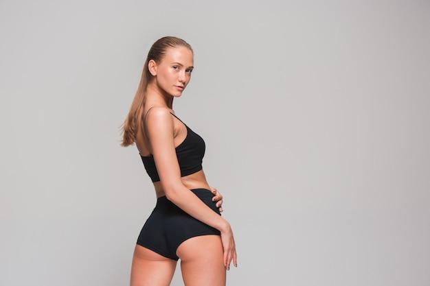 Muskularny sportowiec młoda kobieta na szaro