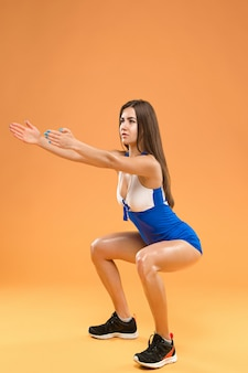 Muskularny sportowiec młoda kobieta pozowanie studio na pomarańczowym tle