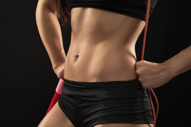 Muskularny sportowiec młoda kobieta z skakanka na czarno