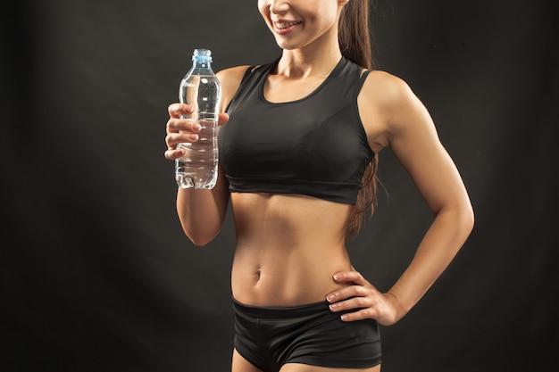 Muskularny sportowiec młoda kobieta z wodą na czarno