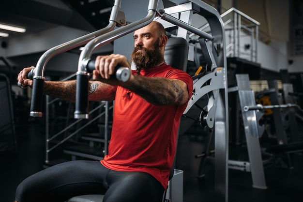 Muskularny sportowiec na maszynie do ćwiczeń w siłowni. brodaty mężczyzna na treningu w klubie sportowym, zdrowy styl życia
