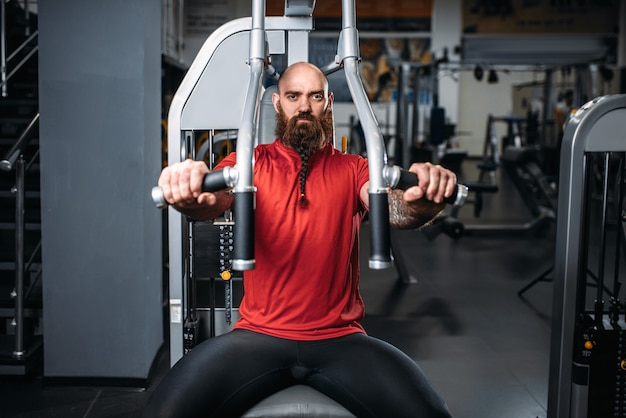 Muskularny sportowiec na maszynie do ćwiczeń w siłowni