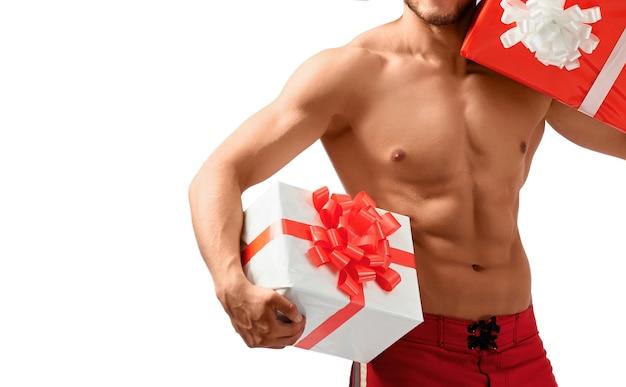 Muskularny święty mikołaj trzyma prezenty
