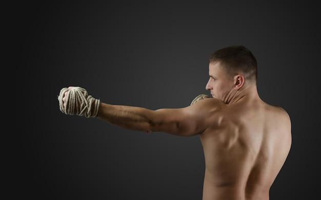 Muskularny wojownik muay thai trenuje na ciemnej powierzchni z linami konopnymi na rękach
