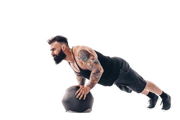 Muskularny wytatuowany brodaty mężczyzna ćwiczeń