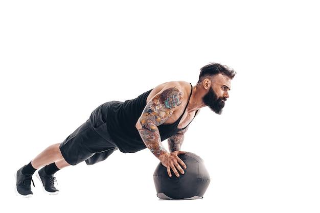 Muskularny wytatuowany brodaty mężczyzna wykonujący ciężary fitness piłka lekarska ćwiczenia pompek