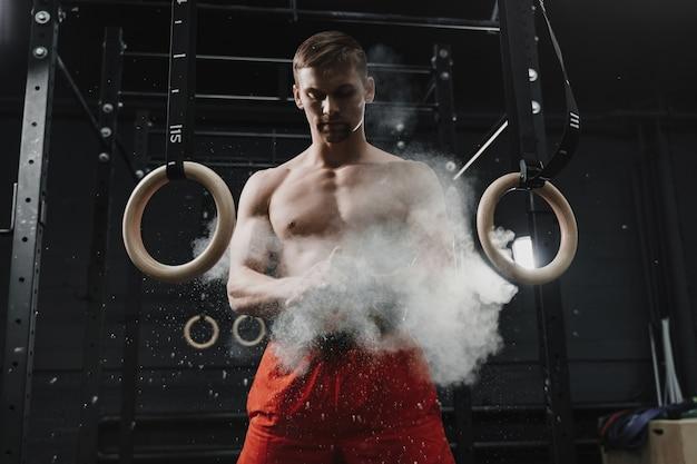 Muskularny zawodnik crossfit, klaszczący w dłonie i przygotowujący się do treningu na siłowni.