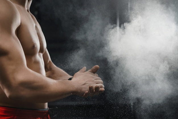 Muskularny zawodnik crossfit, klaszczący w dłonie i przygotowujący się do treningu na siłowni