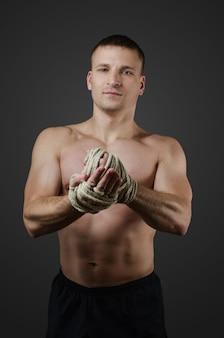 Muskularny zawodnik muay thai walczy rozgrzewkę przed treningiem lub na rękach konopnej liny