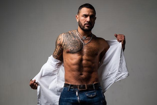 Muskularny, zdrowy, wysportowany pewny siebie mężczyzna macho o atletycznej budowie, zdejmując koszulę.