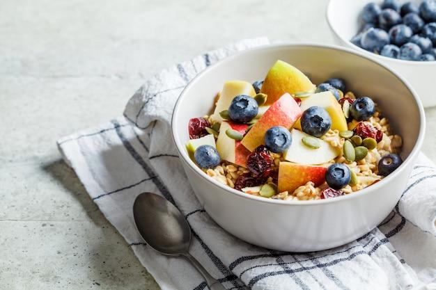 Musli brzozowe lub płatki owsiane na noc z jabłkiem, bananem i jagodami w szarej misce.