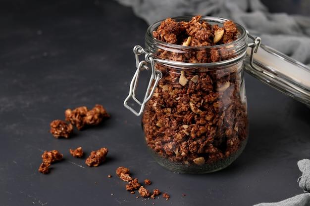 Musli chrupiące musli granola z naturalnym miodem, czekoladą i orzechami w szklanym słoju na ciemnym tle, zdrowa żywność, orientacja pozioma, zbliżenie