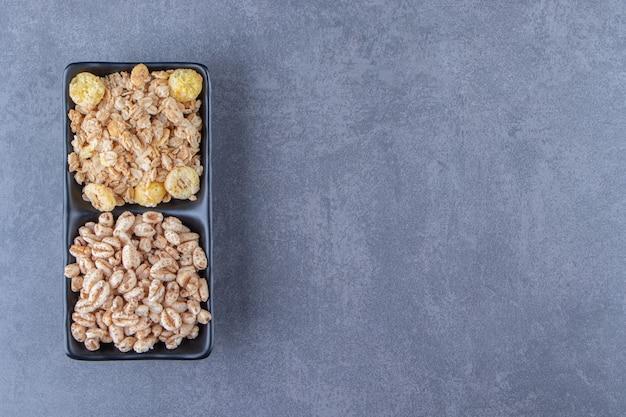 Musli i płatki kukurydziane w miseczkach, na marmurowym tle. zdjęcie wysokiej jakości