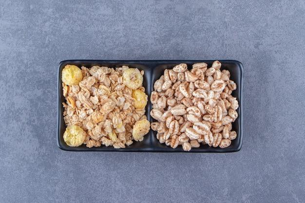 Musli i płatki kukurydziane w miskach, na marmurowym stole.