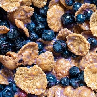 Musli z jagodami i płatkami w czarnej misce, z bliska. zdrowa żywność, koncepcja zdrowego śniadania