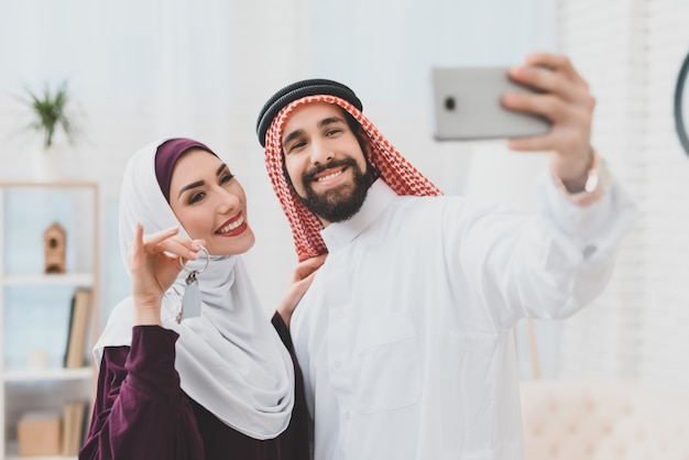 Muslim couple dream home selfie with house keys.