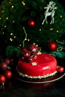 Musowy deser z ciasta świątecznego pokryty czerwoną lustrzaną glazurą z dekoracjami noworocznymi