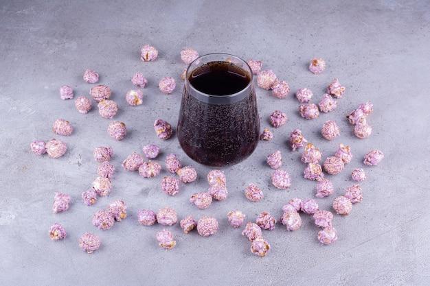 Musująca szklanka coli pośrodku rozrzuconego popcornu na marmurowym tle. zdjęcie wysokiej jakości