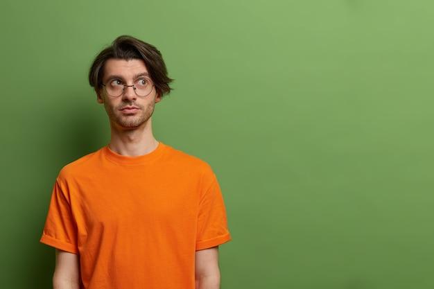 Muszę pomyśleć. zamyślony facet z modną fryzurą wygląda poważnie na bok, rozważa plan lub decyzję, nosi okrągłe okulary i pomarańczową koszulkę, odizolowane na pustej przestrzeni zielonej ściany