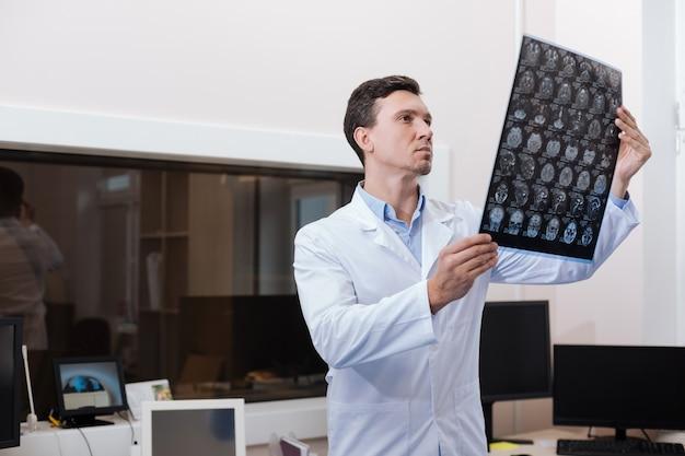 Muszę postawić diagnozę. przystojny, doświadczony miły stój w swoim laboratorium i radiolog oglądający zdjęcia tomografii komputerowej podczas stawiania diagnozy