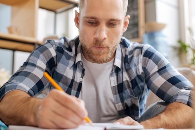 Muszę to zrobić. poważny, rozważny, skupiony mężczyzna trzymający ołówek i rysujący szkic, skupiony na swojej pracy
