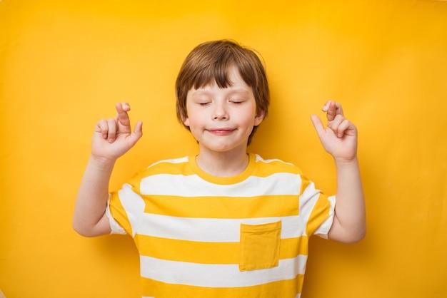Muszę wygrać. wesoły chłopczyk zaciska zęby, podnosi kciuki, spełnia życzenia, nosi codzienne ubrania, czeka na dobre wieści, stoi w domu nad żółtą ścianą