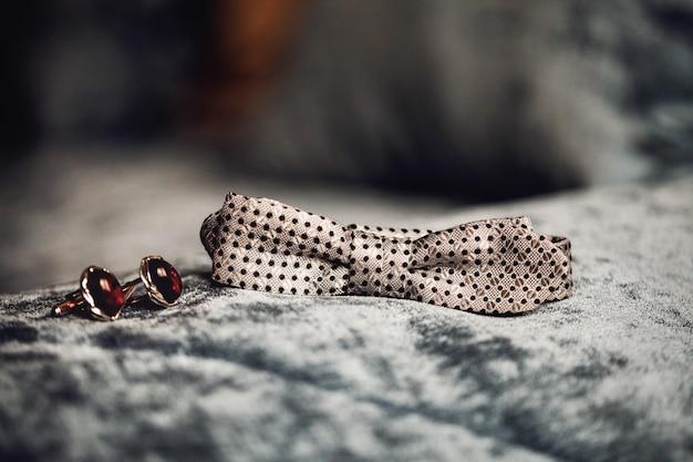 Muszka, obrączki ślubne, spinki do mankietów na tle włókienniczych.