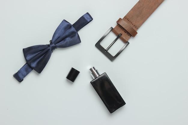 Muszka, pasek, butelka perfum na białym tle. akcesoria męskie. formalny styl, przygotowanie do ślubu.