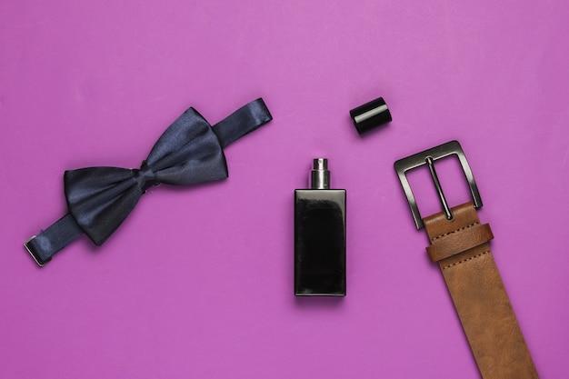 Muszka, pasek, butelka perfum na fioletowym tle. akcesoria męskie. formalny styl, przygotowanie do ślubu.