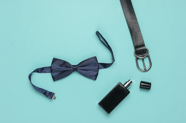 Muszka, pasek, butelka perfum na niebieskim tle. akcesoria męskie, zestaw biznesowy dla mężczyzn. formalny styl, przygotowanie do ślubu.