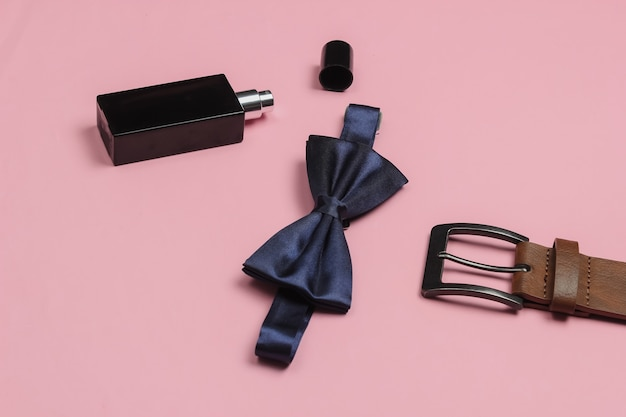 Muszka, pasek, butelka perfum na różowym tle. akcesoria męskie. formalny styl, przygotowanie do ślubu.