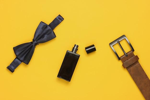 Muszka, pasek, butelka perfum na żółtym tle. akcesoria męskie, zestaw biznesowy dla mężczyzn. formalny styl, przygotowanie do ślubu.