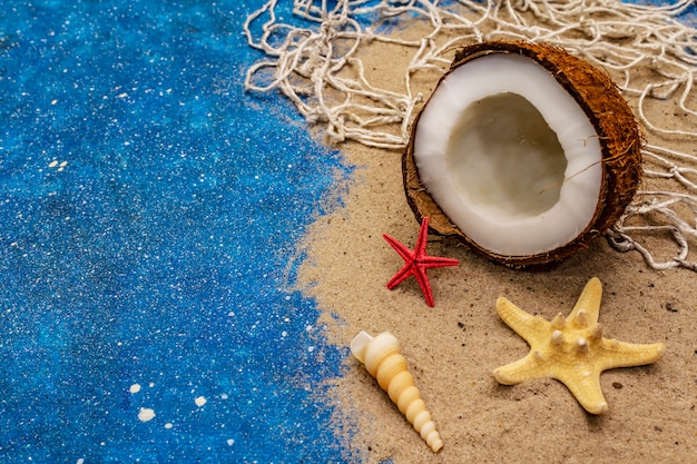 Muszla, rozgwiazdy, lina kokosowa i niebieski blask jak morze