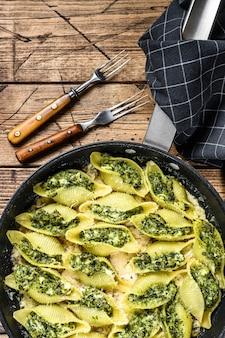 Muszle makaronu conchiglioni nadziewane szpinakiem i serem zapiekane z sosem na patelni na drewnianym stole. widok z góry.