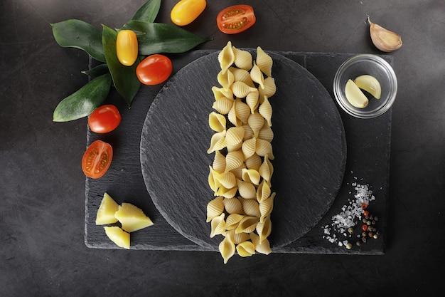 Muszle makaronu na czarnym kamieniu. pomidory i liście laurowe z zielem angielskim i solą morską oraz czosnkiem.