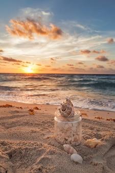 Muszle morskie zebrane w słoiku trawy na tropikalnej piaszczystej plaży ze wschodem słońca nad oceanem