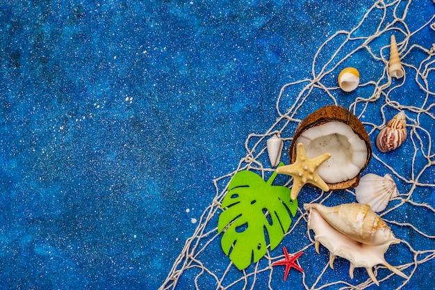 Muszle, siatka, kokos, rozgwiazdy i liść monstera na niebieskim brokacie