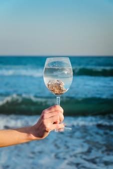 Muszle w szklance w kobiecej dłoni na tle błękitnego morza