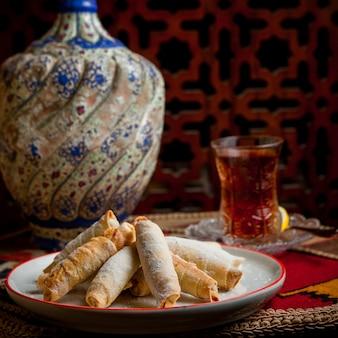 Mutekke widok z boku ze szklanką herbaty, cytryny i wazy w tabeli