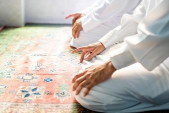 Muzułmańscy mężczyźni modlący się w postawie Tashahhud