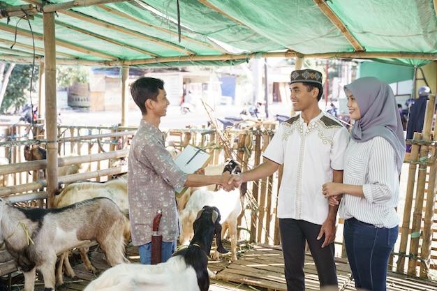 Muzułmanie uściskają rękę z rolnikiem po zakupie kozy. celebracja ofiar idul adha
