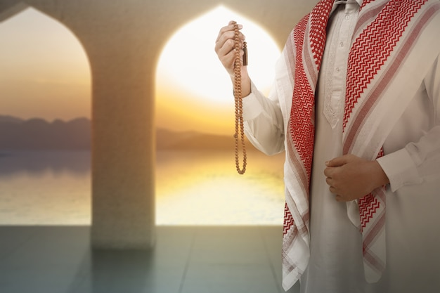 Muzułmanin modlący się z koralikami modlitewnymi na rękach na meczecie