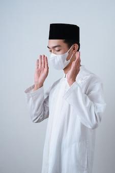 Muzułmanin modlił się przeciwko na szaro z maską