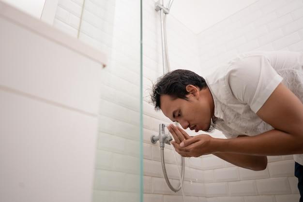 Muzułmanin myje swoje ciało wodą z kranu przed modlitwą. ablucja wudhu czyszczenie