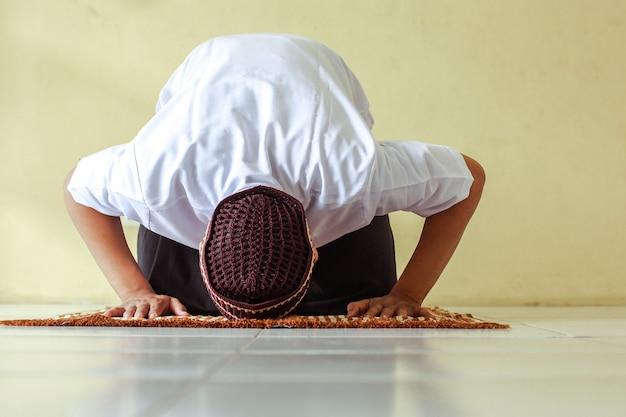 Muzułmanin salat z pokłonami pozie na macie modlitewnej