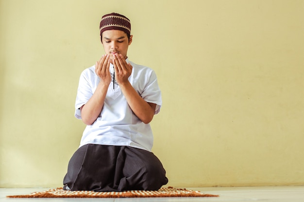 Muzułmanin siedzi z błagającym gestem ręki na macie modlitewnej