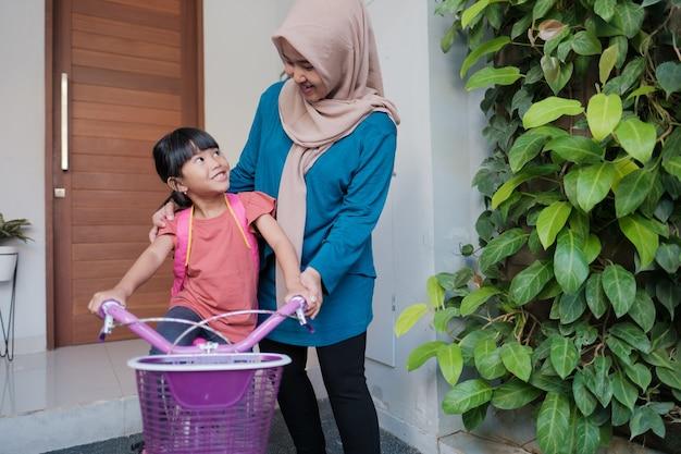 Muzułmanka i jej córka przygotowują się rano do szkoły jadąc na rowerze
